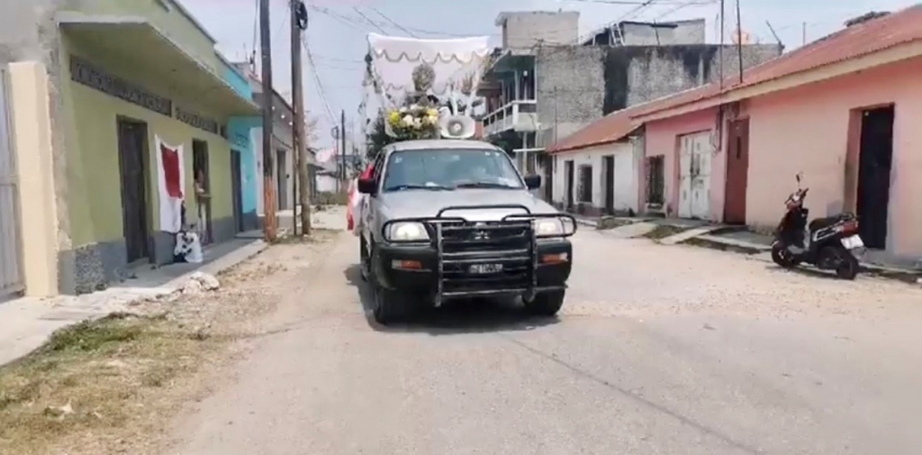 Guatemala - A pickup takes Blessed Sacrament through city streets